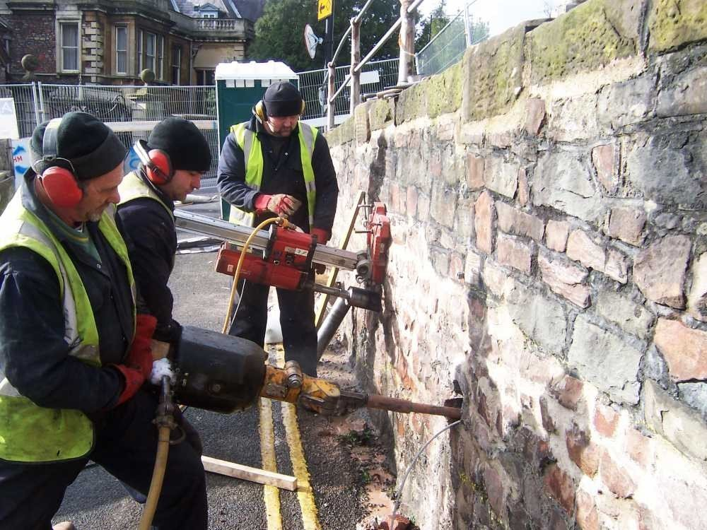 A platipus approved installers driving and loadlocking anchors on a retaining wall