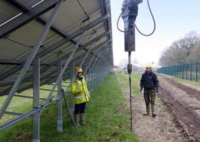 Workers driving a Platius anchor using heavy machinery at the Crossways solar park in Dorset
