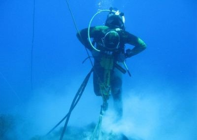 Diver driving a Platious Bat Anchor into the sea bed