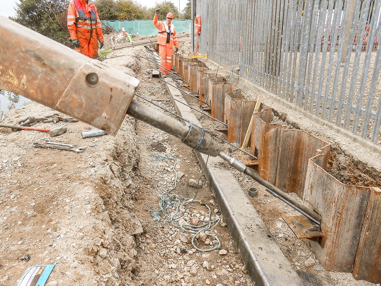 Driving ground anchor into sheet pile